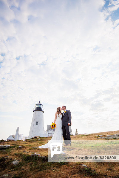 Portrait of married couple kissing,  lighthouse in background