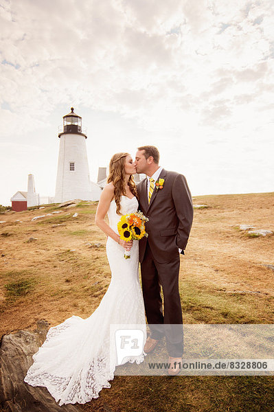 Portrait of married couple kissing  lighthouse in background