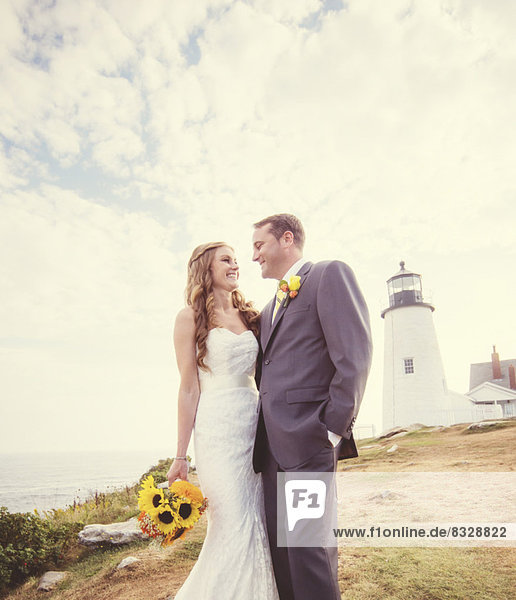 Portrait of married couple  lighthouse in background