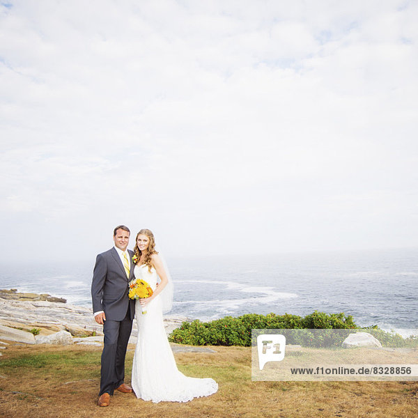Portrait of married couple  sea in background