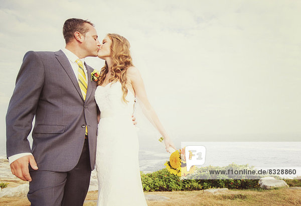 Portrait of married couple kissing  sea in background