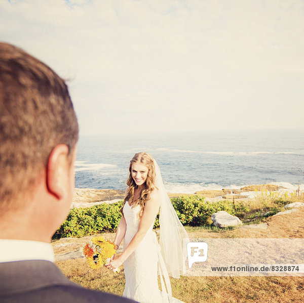 Groom looking at bride  sea in background