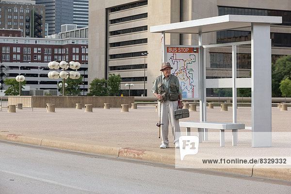 Senior man standing at bus stop with fishing rod
