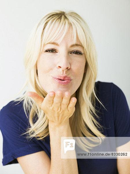 Portrait  Frau  blasen  bläst  blasend  küssen  Studioaufnahme  blond