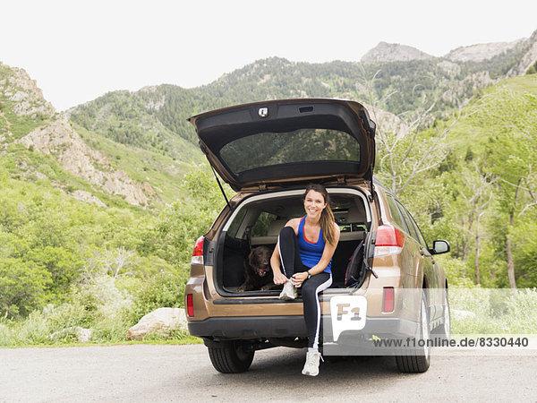 sitzend  Frau  Auto  Hund  Sportkleidung  Kofferraum  Kleidung