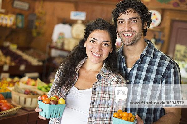Ein Bauernhof  der biologisches Gemüse und Obst anbaut und verkauft. Ein Mann und eine Frau arbeiten zusammen.