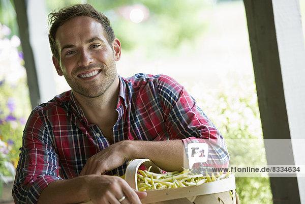 Ein Bauernstand mit frischem Bio-Gemüse und Obst. Ein Mann hält einen vollen Korb mit Bohnen.