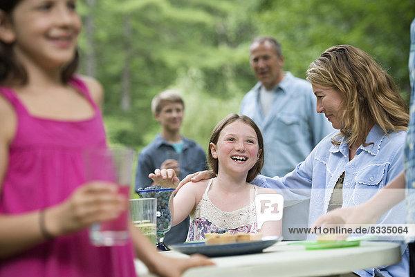 Biologische Landwirtschaft. Eine Familienfeier im Freien mit Picknick. Erwachsene und Kinder.