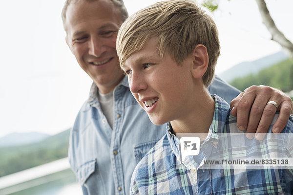 Eine Familie im Freien unter den Bäumen an einem Seeufer. Vater und Sohn.