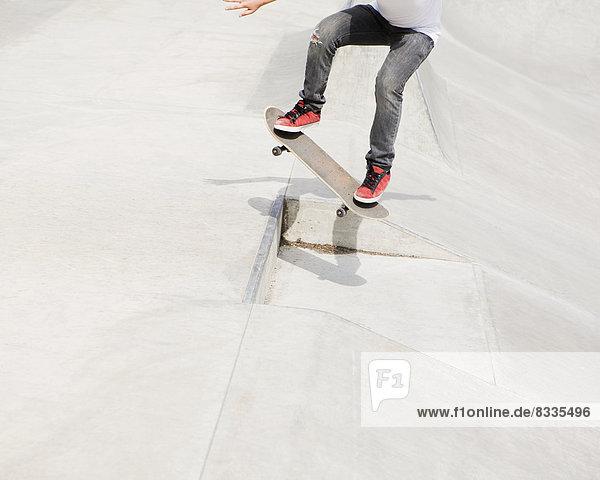 Ein Teenager  der in der Stadt auf einem Skateboard balanciert.