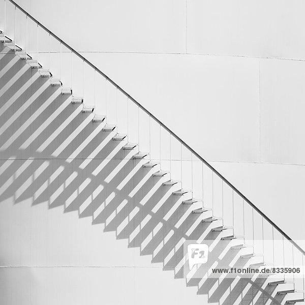Stufen  die an der Seite eines weißen Lagertanks in einer Ölraffinerieanlage nach oben führen. Ein Muster von Schatten. Stufen, die an der Seite eines weißen Lagertanks in einer Ölraffinerieanlage nach oben führen. Ein Muster von Schatten.