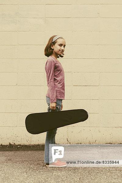 Ein zehnjähriges Mädchen mit einer Geige in einem Koffer auf einer städtischen Straße.