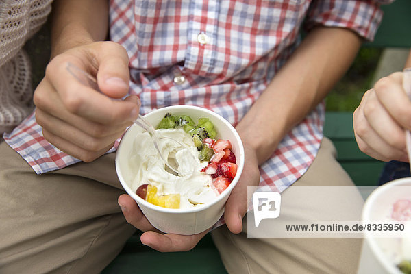 Young people sitting side by side  eating fresh organic fruit and yoghurt desert.