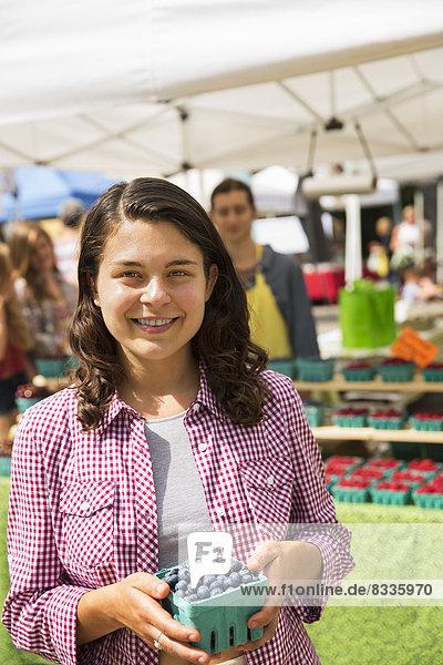 Ein junges Mädchen an einem Bauernstand mit einem Kübel Blaubeeren.