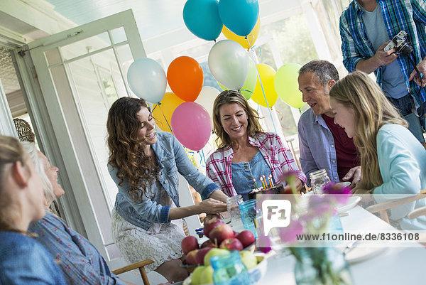 Eine Geburtstagsfeier in einer Bauernküche. Eine Gruppe von Erwachsenen und Kindern versammelte sich um einen Schokoladenkuchen.