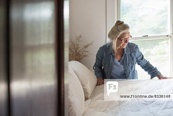 Ein Bauernhaus auf dem Land  Eine Frau macht ein Bett in einem Schlafzimmer.