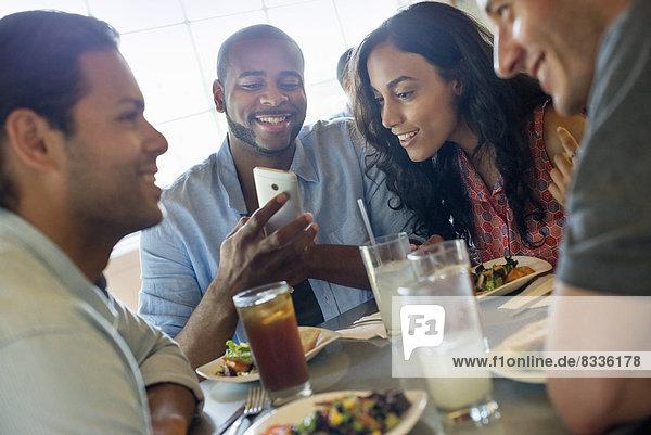 Eine Gruppe von Männern und Frauen in einem Café  die etwas trinken und die Gesellschaft des anderen genießen.