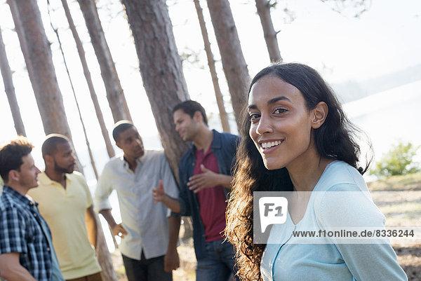 Lakeside. Eine Gruppe von Menschen und Freunden versammelte sich im Sommer im Schatten von Kiefern.
