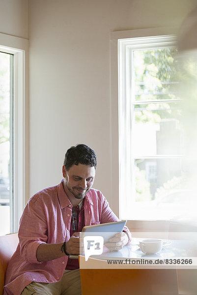 Ein Mann sitzt an einem Café-Tisch und benutzt ein digitales Tablett.