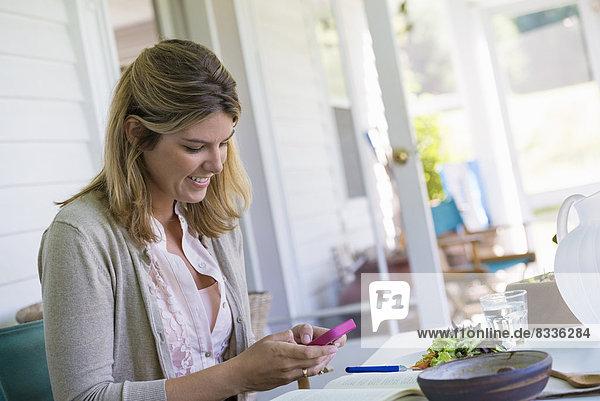 Eine Frau  die mit einem Smartphone an einem Tisch sitzt.