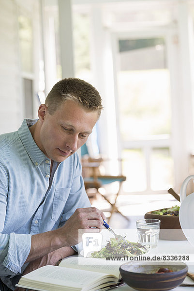 sitzend Mann Buch Salat Cafe essen essend isst Taschenbuch Tisch vorlesen
