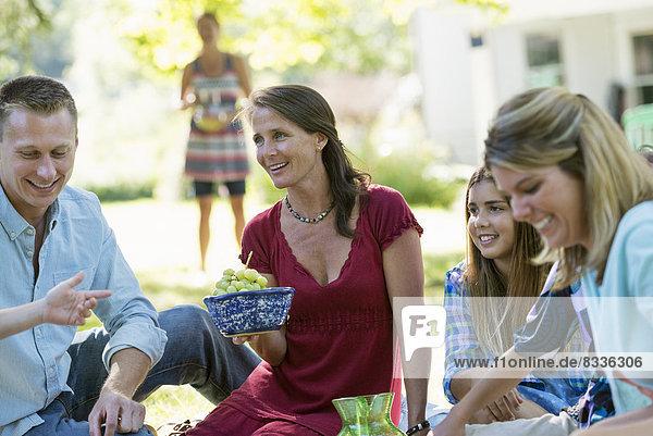 Eine Gruppe von Erwachsenen und Kindern sitzt auf dem Gras im Schatten eines Baumes. Eine Familienfeier.