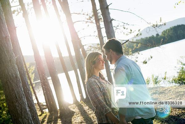 Ein Paar  das in einem Wald am Ufer eines Sees spazieren geht.
