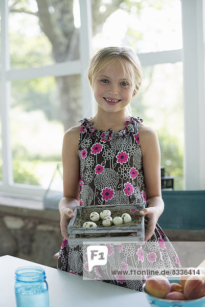 A young girl in a floral dress  examining a clutch of speckled bird eggs in a box.