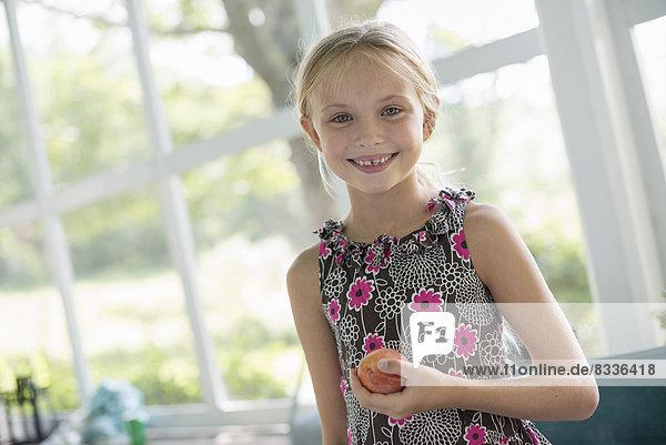 Ein junges Mädchen in einem Blumenkleid  das eine Pfirsichfrucht hält.