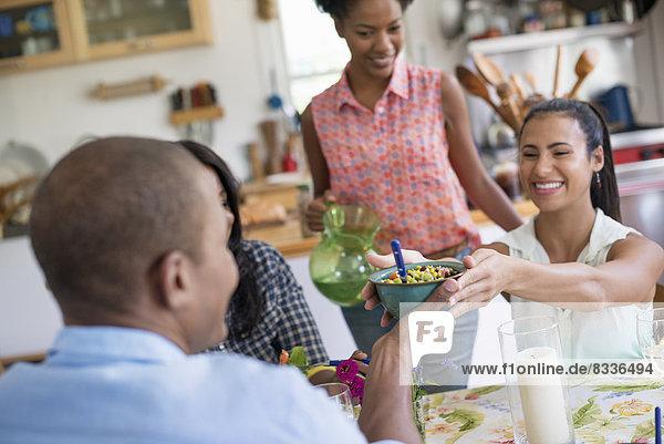 Eine Gruppe von Frauen und Männern bei einer Mahlzeit in einer Bauernküche.