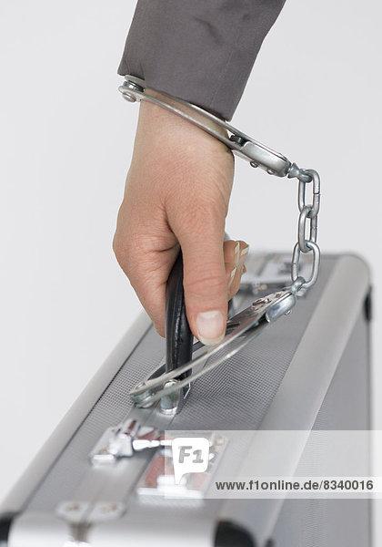 Hand ist mit Handschellen an Alukoffer gefesselt