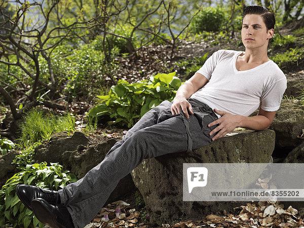 Mann sitzt auf einem Felsen in einem Garten  Provinz Ontario  Kanada