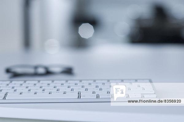Tastatur und Brille auf dem Schreibtisch