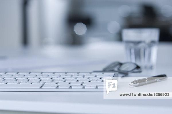 Tastatur auf Schreibtisch  Wasserglas  Kugelschreiber und Brille