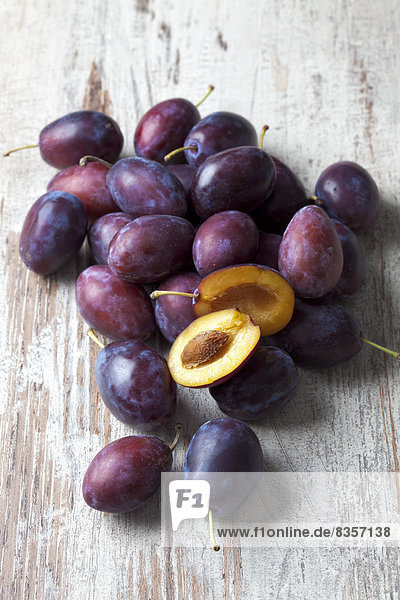 Pflaumen (Prunus domestica) auf Holztisch  Studioaufnahme