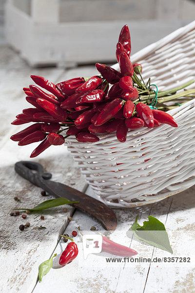 Rote Chilischoten (Capsicum) im weißen Korb auf weißem Holztisch  Studioaufnahme