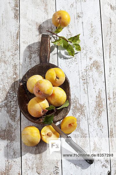 Geschnittene und ganze gelbe Lehren (Prunus domestica subsp. italica) und ein Holzlöffel auf weißem Holztisch  Studioaufnahme