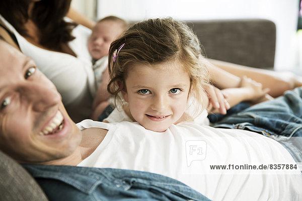 Junge Eltern mit männlichem Neugeborenen und kleiner Tochter,  die zu Hause auf dem Sofa sitzt.