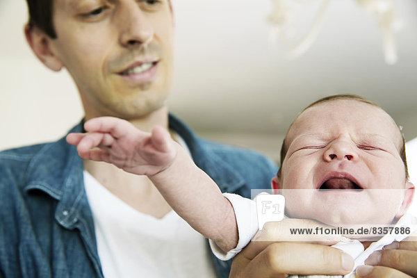 Junger Vater hält seinen weinenden  neugeborenen Sohn.