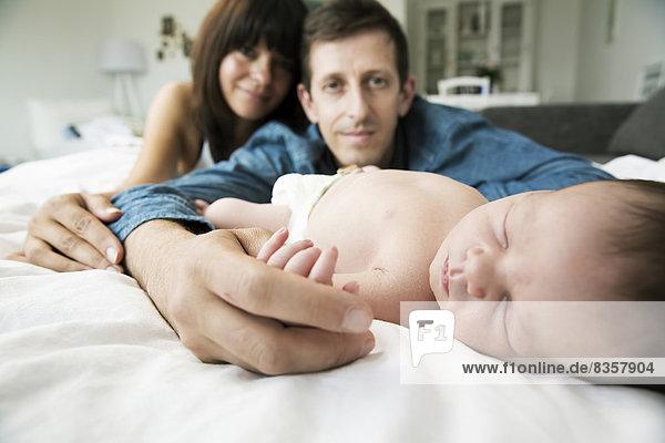 Junge Eltern mit ihrem neugeborenen Sohn zu Hause