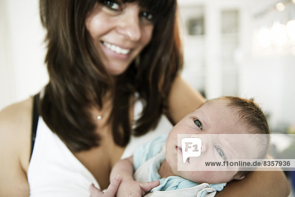 Smiling young mother carrying her newborn son in her arms