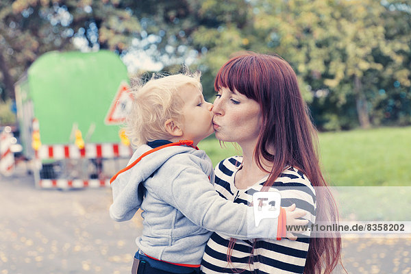 Baby boy kissing mother