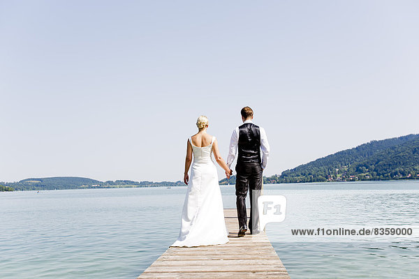 Germany  Bavaria  Tegernsee  Wedding couple standing on jetty