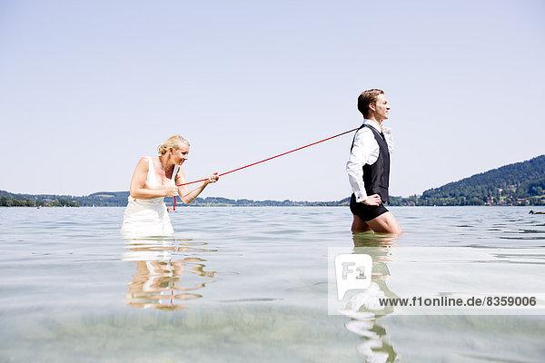 Germany  Bavaria  Tegernsee  Wedding couple standing in lake  bride holding groom on leash
