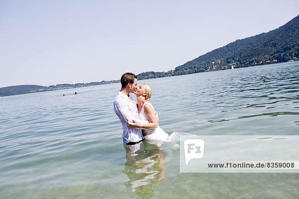 Germany  Bavaria  Tegernsee  Wedding couple standing in lake  kissing