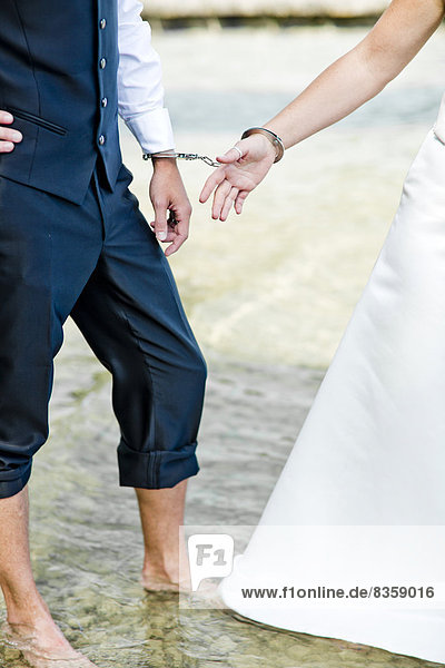 Germany  Bavaria  Tegernsee  Wedding couple standing in lake  wearing hand cuffs