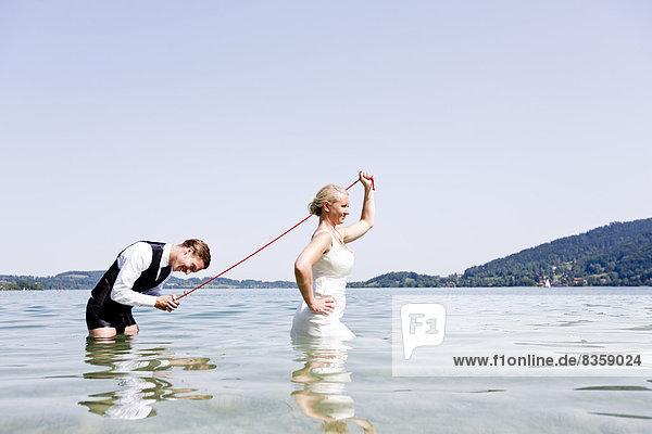 Deutschland  Bayern  Tegernsee  Hochzeitspaar im See stehend  Brautpaar mit Bräutigam an der Leine