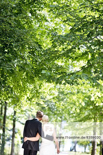 Deutschland  Bayern  Tegernsee  Hochzeitspaar unter Bäumen