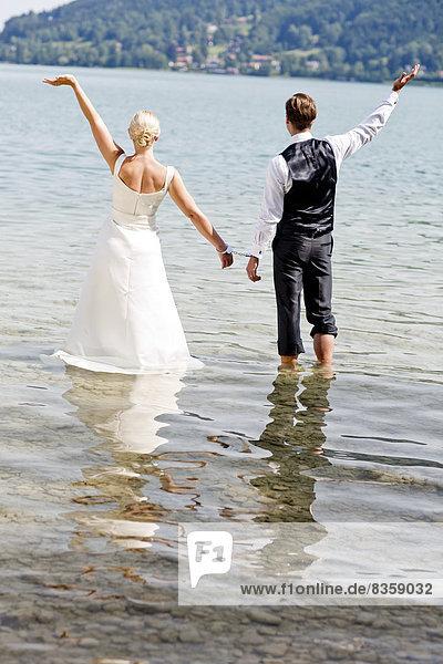 Deutschland  Bayern  Tegernsee  Hochzeitspaar im See stehend mit Handschellen