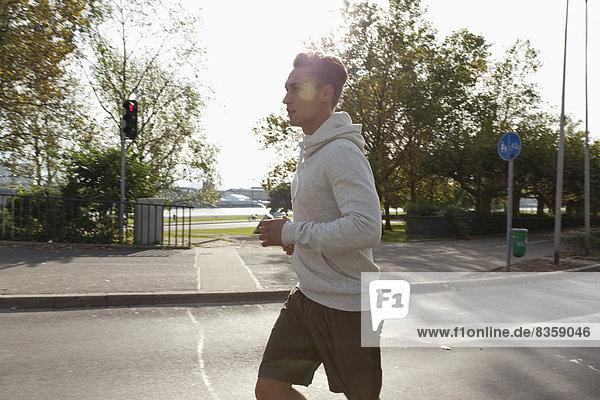Germany  North Rhine Westphalia  Duesseldorf  Mid adult man jogging